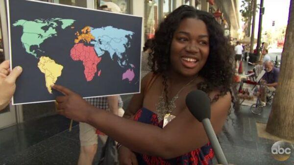 Una chica señalando el lugar en el que cree que está Corea del Norte en un mapa