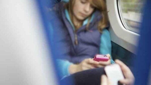 Adolescente en el tren con el móvil