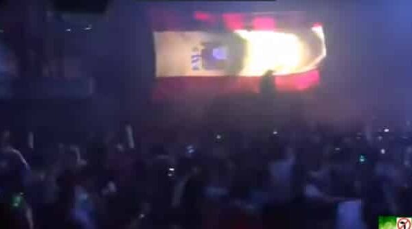 Jóvenes tarareando el himno de España en una discoteca