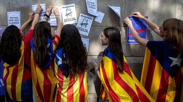 Jóvenes con esteladas y pegando carteles a favor del referéndum ilegal