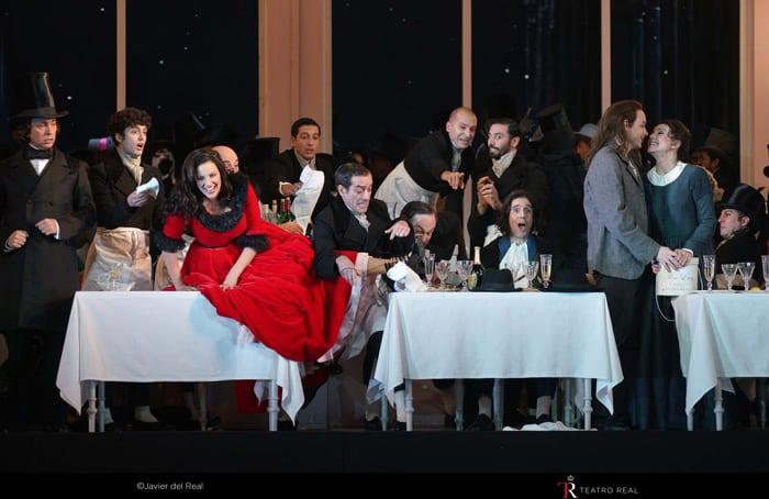 Plano general del 2º acto, con la soprano Joyce El-Khoury ('Musetta'), en rojo, el Coro Titular del Teatro Real, barítono Joan Martín-Royo ('Schaunard'), la soprano Anita Hartig ('Mimì') y el tenor Stephen Costello ('Rodolfo'), a la derecha.