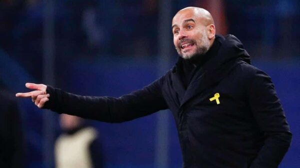 Pep Guardiola luciendo el lazo amarillo durante un partido