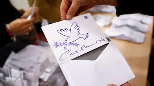 """Un miembro de la mesa electoral muestra un voto nulo con el dibujo de una paloma y el lema """"paz"""" en varios idiomas"""