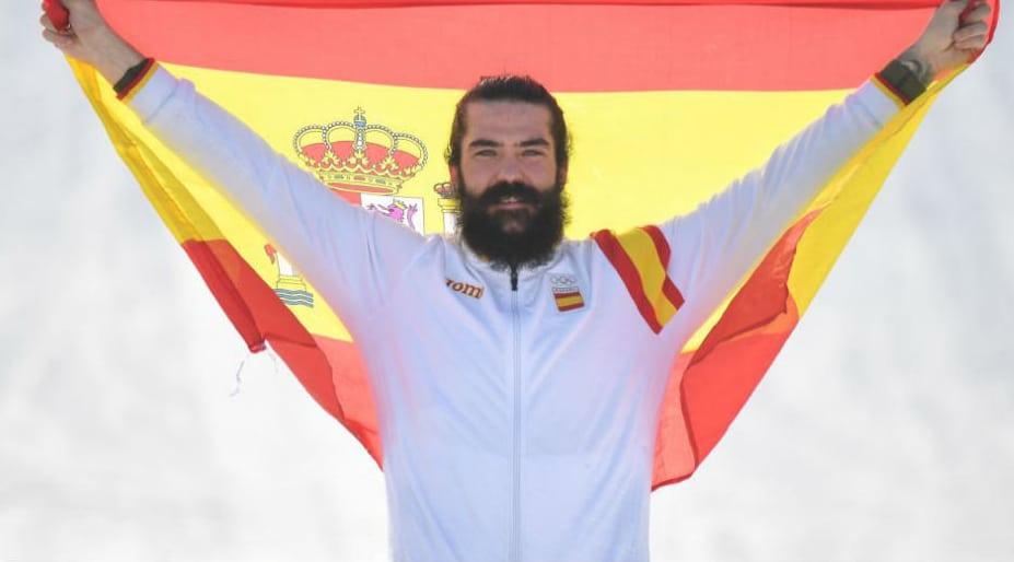 Regino Hernández celebra su medalla olímpica en el podio con la bandera de España