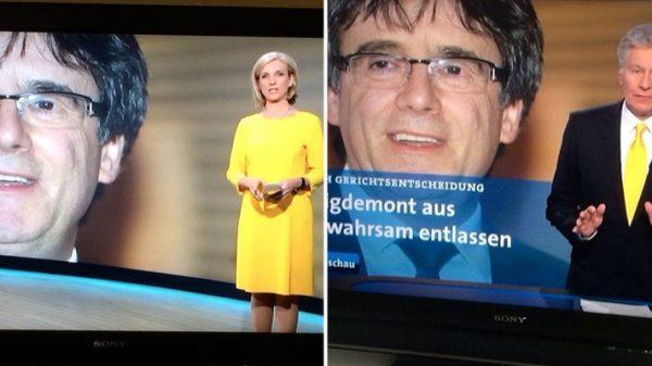 Dos presentadores de la televisión pública alemana con prendas amarillas informando sobre Puigdemont