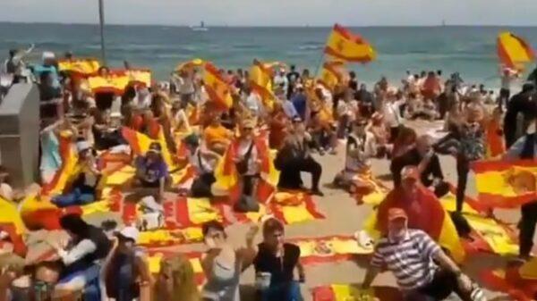 Banderas y toallas españolas en una playa catalana