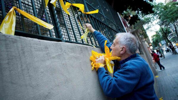 Un miembro de un GDR retirando los lazos amarillos que han puesto los CDR