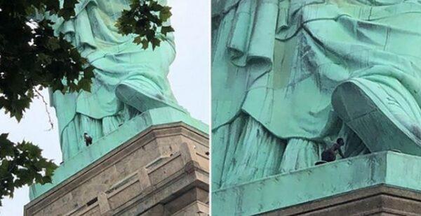 La mujer subida en las faldas de la Estatua de la Libertad