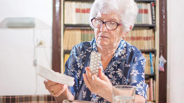 Persona mayor consulta el prospecto de un medicamento